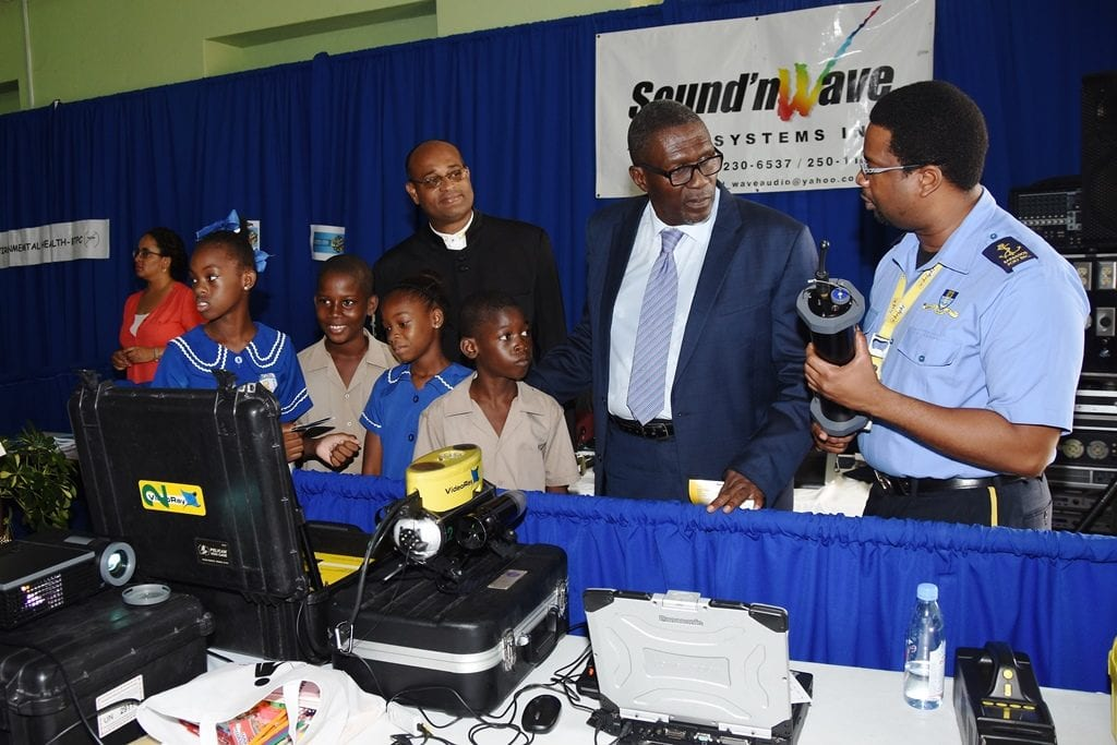 Senator Harry Husbands; Minister of State in the Office of the Prime Minister, Senator Patrick Todd and Wesley Hall Junior students visiting the display both of the Barbados Port Authority at today's Career Showcase. (C.Pitt/BGIS)