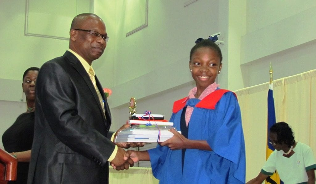 Top girl in the Barbados Secondary Schools' Entrance Examination, Azaria Johnson presented with some of her prizes by Anthony Gittens. (GP)