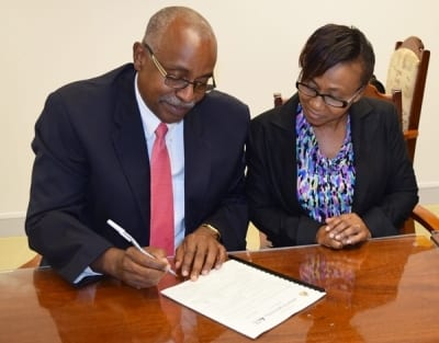 Principal Consultant at ibiz, Dr. André Vincent Henry signs the contract for the Monitoring and Evaluation System project, as Permanent Secretary, Janet Phillips looks on. (Photo by Willie Parris-OAS Barbados)