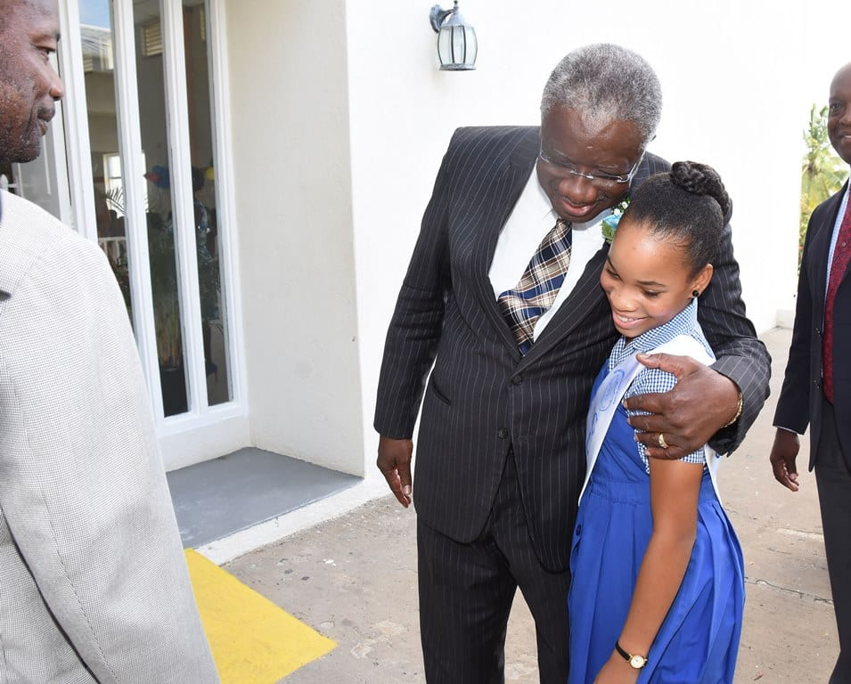Prime Minister Freundel Stuart hugging one of the graduates of the Reynold Weekes Primary at today's ceremony while Principal, Anderson Bishop (left) looks on. (C.Pitt/BGIS)