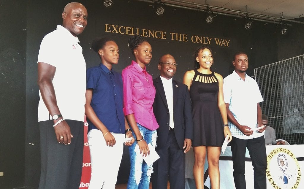Sports Minister, Stephen Lashley (centre) and Olympic gold medallist, Carl Lewis (left) pose with the four scholarship winners: (l-r) Kylia Smith; Jalicia Neil; Jade Searles; and Kemar Cumberbatch. (J.Weekes/BGIS)