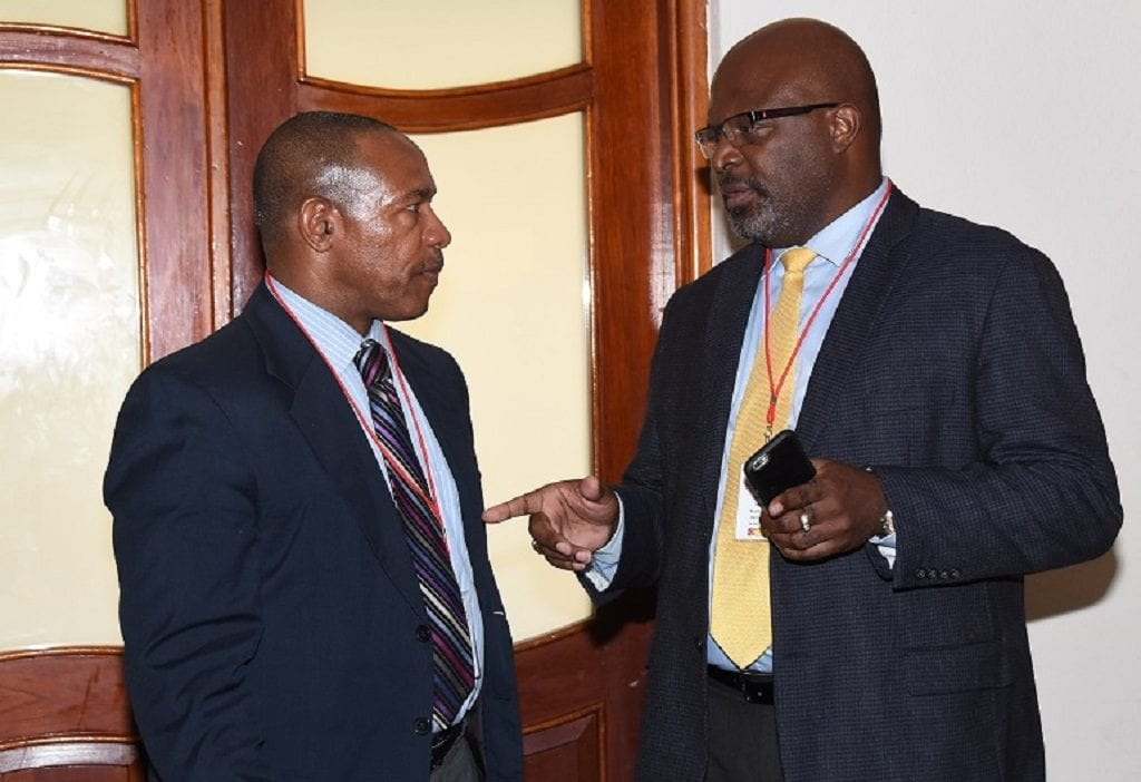 Minister of Home Affairs, Adriel Brathwaite (right) chatting with Caribbean Postal Union Secretary General, Allan Wayne Smith during a break in today's conference. (C.Pitt/BGIS)