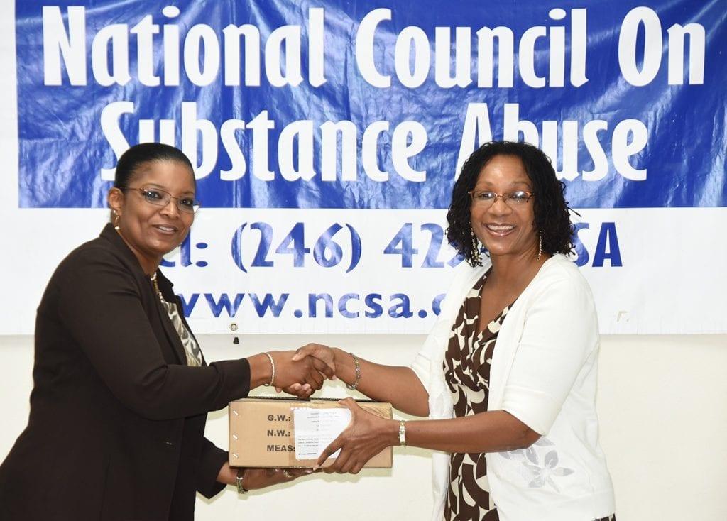 NCSA Manager, Betty Hunte (left) presenting Principal of the Edna Nicholls Centre, Debra Hewitt with drug testing kits at the one-day drug eradication workshop. (C.Pitt/BGIS)