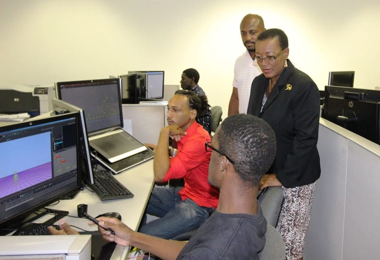 Senator Maxine McClean engaging some of the animation students last Friday while touring the BIMAP Animation Training Laboratory, as CEO of West Toonz, Curtis Padmore looks on. (D.Gittens/BGIS)