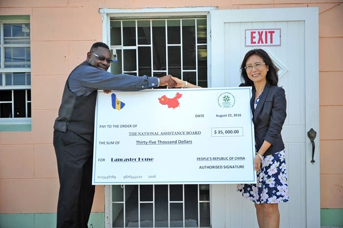 China's Ambassador to Barbados, Wang Ke presenting the $35,000 cheque to Social Care Minister, Steve Blackett, this morning at Lancaster House, St. James. (A.Miller/BGIS)