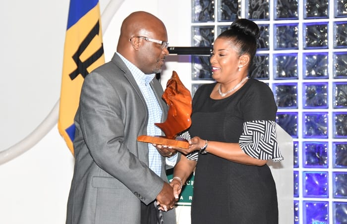 Attorney General and Minister of Home Affairs, Adriel Brathwaite receiving the Foundation Builder Award from NCSA Manager, Betty Hunte at the organisation's 21st anniversary awards and recognition ceremony at the Accra Beach Resort and Spa on Saturday. (C.Pitt/BGIS)