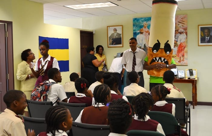 Research and Information Officer, Jonathan Yearwood, standing next to Ziggy the Cigarette, speaking to students during one of the NCSA's activities. (NCSA)