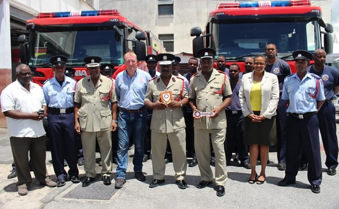 Acting Deputy Chief Fire Officer, Llyodson Phillips (third from left); Service Supervisor at Angloco Limited, Dave Stone; Chief Fire Officer, Errol Maynard and Divisional Officer in Charge of the Northern Division and Fleet Maintenance, Ormond Fenty, during yesterday's handover; as other fire officers look on. (GP)