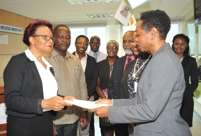 Attorney-at-Law, Tammy L. Bryan of George Walton Payne Associates presenting CAIPO Registrar, Heather Clarke with the first Geographical Indication Application while Minister Donville Inniss and Ministry officials look on. (A.Miller/BGIS)