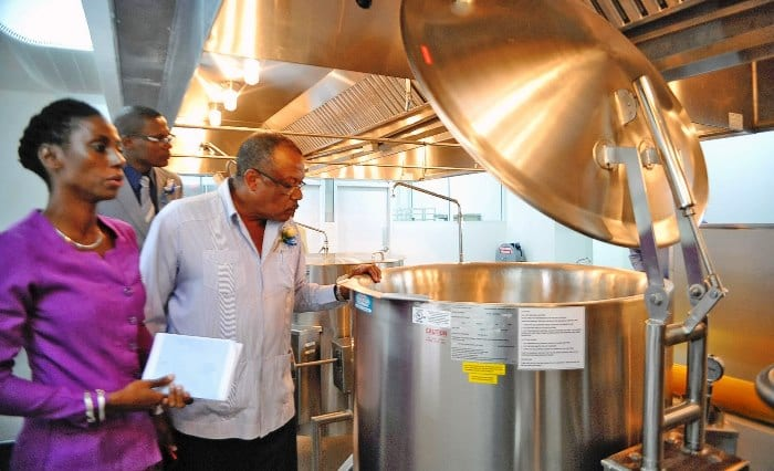 Health Minister, John Boyce examining some of the newly installed equipment in the kitchen at the Psychiatric Hospital. At left is Sales Executive at ESSCO, Vaughndeen Harper and in the background is Hospital Director, David Leacock. (A.Miller/BGIS)
