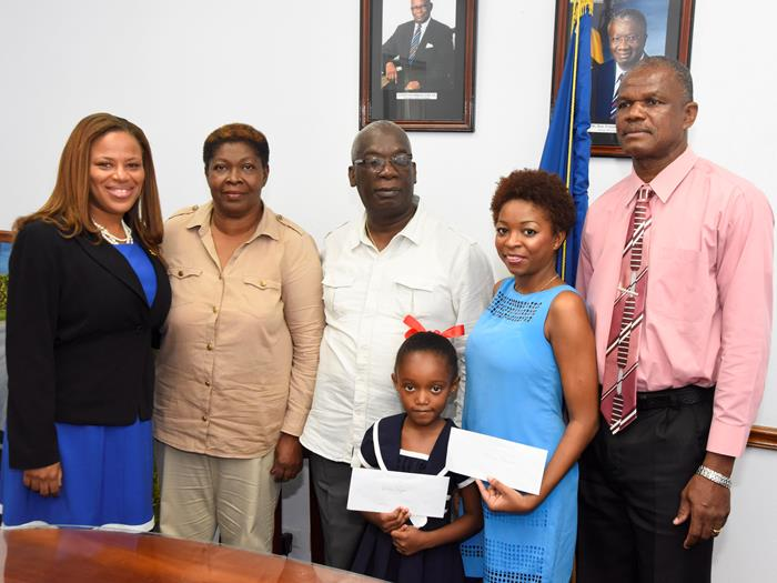 Education Minister, Ronald Jones (centre) posing with this year's awardees, Ariah Abigail Rogers (second right) and Dionna Browne (front) as well as the 2014 Melanie Kristin Price scholarship winner, Shelly-Anne Smith (left); Chairperson of the Foundation and Melanie's mother, Yvette Oxley (second left) and Glyne Price, father of the late Melanie Price. (E.Walker)