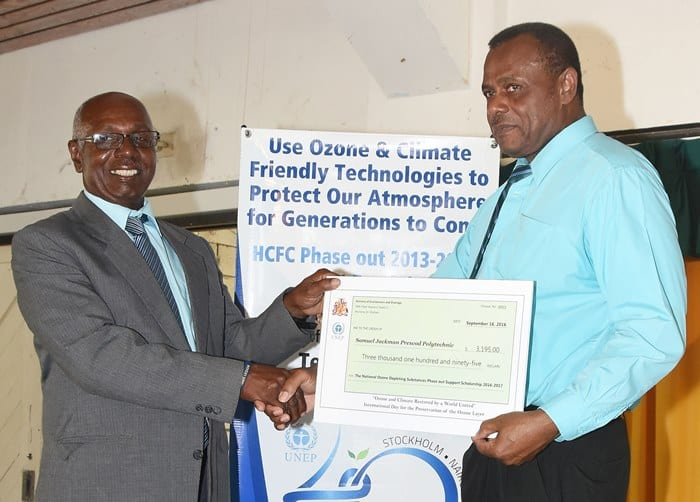 Permanent Secretary in the Ministry of the Environment, Edison Alleyne (right) presenting a cheque to SJPP Principal, Hector Belle at today's MOU signing ceremony. The funds will be used to provide support for the institution's refrigeration and air conditioning diploma programme. (C.Pitt/BGIS)