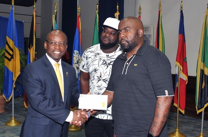 "Culture Minister, Stephen Lashley presenting Darin Holder with his BDS $10,000 cheque for winning the CARIFSTA XIII jingle competition today. Looking on is music producer Dwain ""Dwaingerous"" Antrobus who helped Mr. Holder with the jingle. (A.Miller/BGIS)"