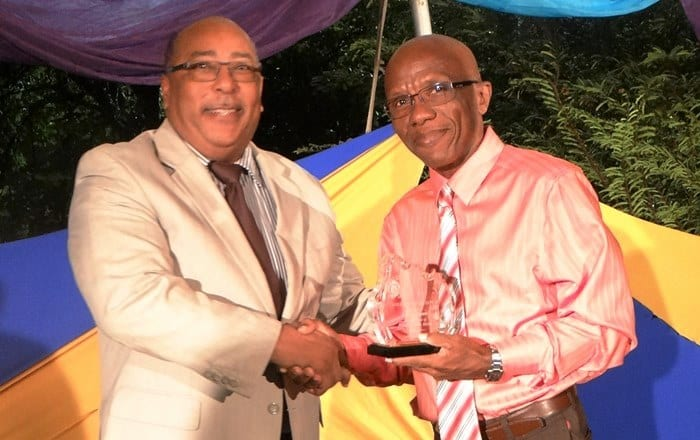 Minister of Agriculture, Dr. David Estwick presenting retired Senior Animal Health Assistant, Errol Gill-Moore with token of appreciation for 39 years of service to the Ministry. (Photo compliments the Ministry of Agriculture.)