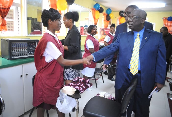 Education Minister, Ronald Jones greets one of the cosmetology students Looking on is (A.Miller)