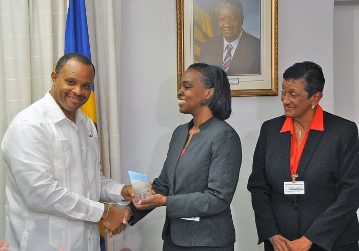 CCRIF Director, Faye Hardy presenting Minister of Finance and Economic Affairs, Christopher Sinckler with the payout memento while CCRIF Board Member, Desiree Cherebin, looks on. (A.Miller/BGIS)