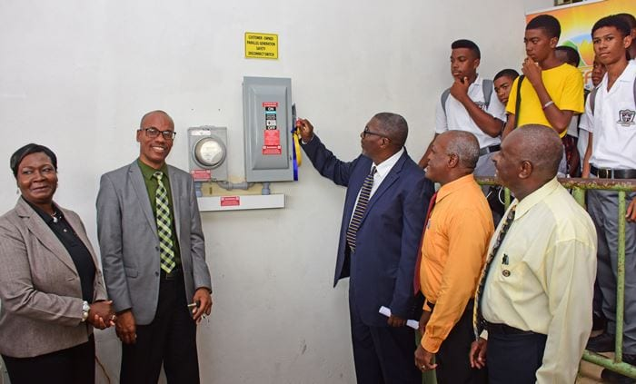 Parliamentary Secretary in the Ministry of Education, Science, Technology and Innovation, Senator Harcourt Husbands, flicking the switch to turn on the photovoltaic system at the St. Leonard's Boys' School last Friday. Looking on are: (BGIS)