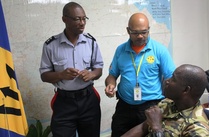 Police Inspector, Fred Clarke; Acting Deputy Director of the Department of Emergency Management, Captain Robert Harewood; and in discussion at the National Emergency Operations Centre (A.Skeete/BGIS)