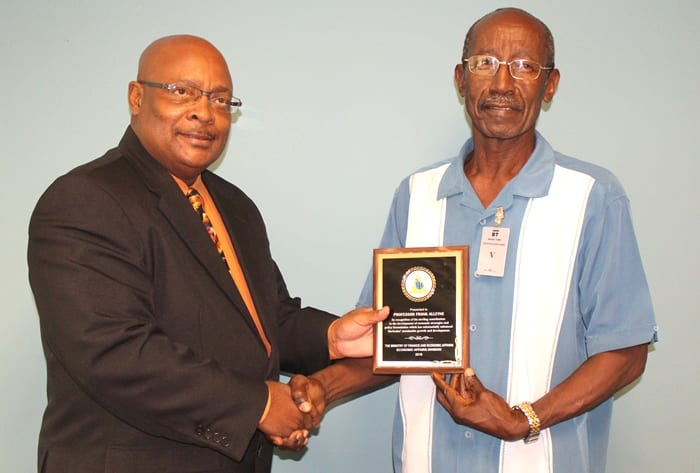 Parliamentary Secretary in the Ministry of Finance and Economic Affairs, Senator Jepter Ince presenting Sir Frank Alleyne (Photograph compliments the Barbados Advocate)