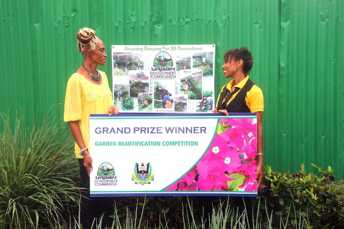 UDC Project Officer, Paula Gall (right) making a presentation to winner of the Commission's 2016 Garden Beautification Competition, Marcia Springer today. (C.Henry/BGIS)