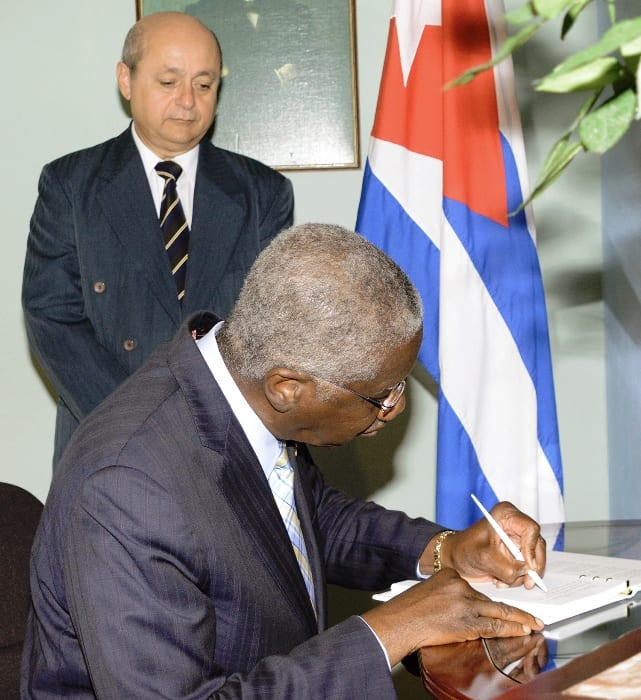 Prime Minister Freundel Stuart signing the Book of Condolence while Ambassador Francisco Fernandez Pena looks on. (A. Gaskin/BGIS)