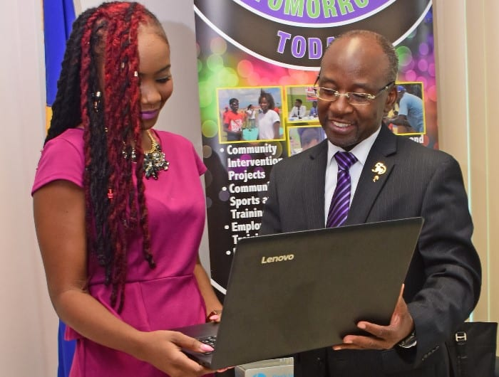 Minister of Youth Affairs, Stephen lashley, showing Claypso Queen, Aziza Clarke, the feature of the Lenovo laptop during the presentation yesterday at the Ministry of Culture Sports and Youth. (C.Pitt/BGIS)