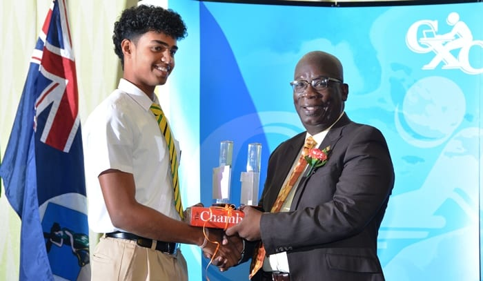 Education Minister, Ronald Jones presenting Kayshav Tewari of Queen's College, Guyana with his prize for The Most Outstanding Candidate in the May/June CSEC examinations. (B.Hinds/BGIS)